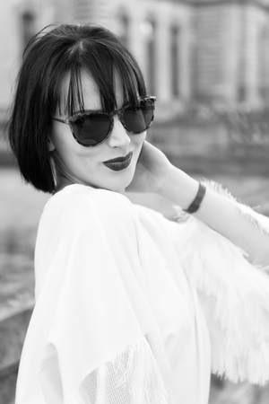 Hide her emotion behind sunglasses. Girl brunette bob hairstyle looks stylish. Girl fashionable lady with bob hairstyle outdoor urban architecture background. Woman fashionable model posing outdoor.