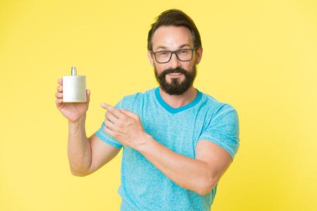 Beneficios asombrosos del uso de perfumes. Hombre barbudo guapo mantenga botella de perfume. Cómo elegir el perfume para hombre según la ocasión. Asegúrese de oler fresco durante todo el día. Usar perfume mejora el estado de ánimo. Foto de archivo