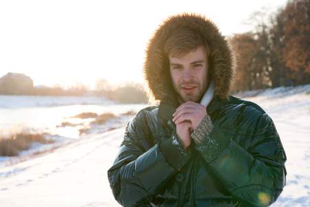 Man traveling in winter, nature. Warm clothes for cold season. Sexy man in winter clothes. Winter fashion. Green warm coat. Happy winter holidays. Flu and cold. Frozen and mystical.