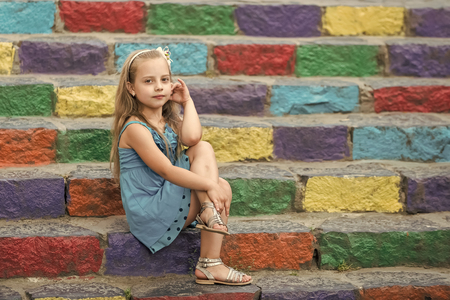 Niña pequeña o niño lindo con cara adorable y lazo en cabello rubio con vestido azul sentado al aire libre en el fondo de coloridas escaleras pedregosas, espacio de copia Foto de archivo