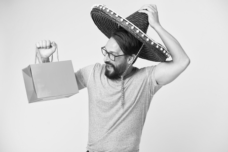 Man cheerful face sombrero hat holds shopping bag yellow background. Guy with beard festive in sombrero. Man festive mood holds shopping bag. Seasonal sale and discount. Holiday and gift concept.