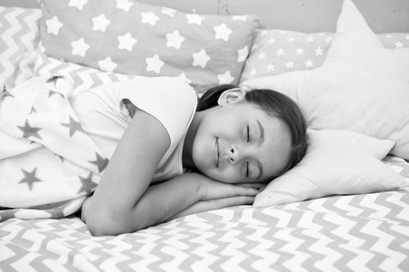 Girl child fall asleep on pillow. Quality of sleep depends on many factors. Choose proper pillow to sleep well. Girl lay on pillow bedclothes background. Child having nap. Cute badclothes and pillows.