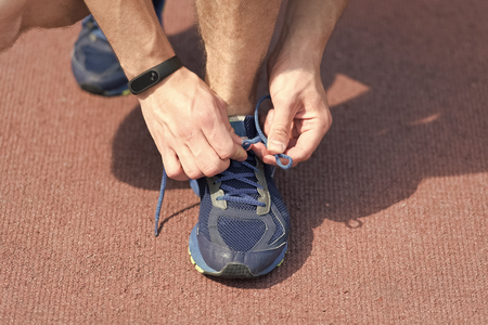 Hands tying shoelaces on sneaker, running surface background. Hands of sportsman with pedometer tying shoelaces on sporty sneaker. Running equipment concept. Shoelaces tying by male hands.