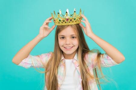 Gute Elternschaft. Kinderbetreuung. Familie und Liebe. Kindertag. glückliches kleines Mädchen auf blauem Hintergrund. kleines Mädchenkind. Schulische Ausbildung. Kindheitsglück. kleines Fräulein in der Krone. Kleiner Gewinner.