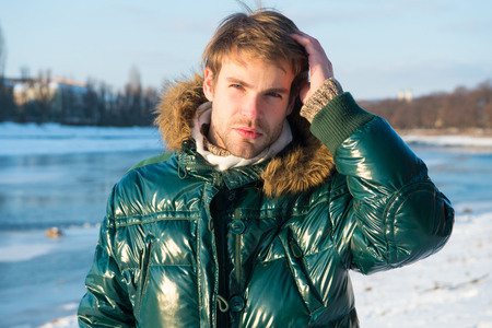 Happy winter holidays. Flu and cold. Winter fashion. Green warm coat. Warm clothes for cold season. Man traveling in winter, nature. Sexy man in warm clothes. Winter activities. Feeling warm.