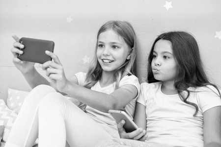 Kids taking selfie in bedroom. Pajamas party concept. Girlish leisure happy childhood. Girls long hair with smartphones use modern technology. Lets take selfie. Send photo your friends social network.