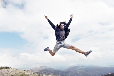 bearded man, long beard, brutal caucasian hipster with moustache jump with happy face on mountain top with cloudy sky, unshaven guy with stylish hair getting beards haircut on natural background 写真素材 - 121261687