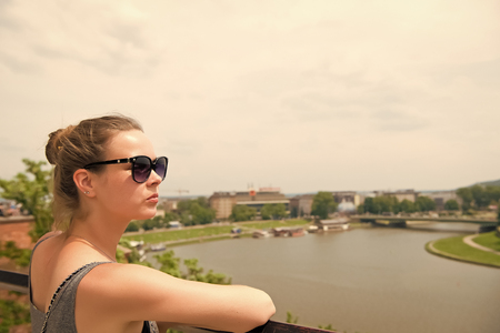 Woman look at vistula river in krakow, poland. Sensual woman in sunglasses on sunny day. Summer vacation concept. Wanderlust, travelling and discover.