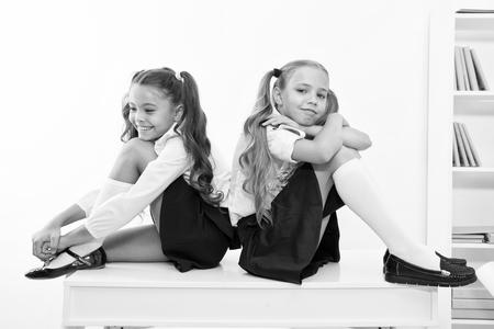 Konzept der Schulpause. Schulmädchen süße Pferdeschwanzfrisur sitzen auf dem Schreibtisch. Beste Freunde kostenlos entspannen nach dem Unterricht. Perfekte Schulmädchen mit ordentlichen, schicken Haaren, die sich nach dem Unterricht entspannen oder ausruhen.