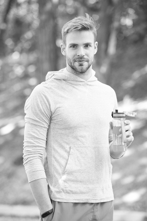 Refreshing vitamin drink after outdoor workout. Man athletic appearance holds water bottle. Guy athlete hold bottle care hydration body after workout. Athlete drink water after training in park.