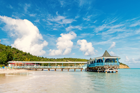 Pier in turquoise water on blue sky background. Sea beach with wooden shelter on sunny day in antigua. Summer vacation on caribbean. Wanderlust, travel, trip. Adventure, discovery, journey.