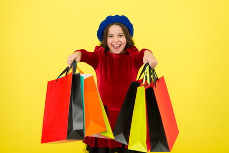 All i want for my birthday. Kid girl hold bunch shopping bags or birthday gifts packages. Birthday shopping concept. Child cute small girl on shopping tour. Best price. Buy now. Visit shopping mall.