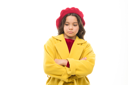 Sad child. Sadness concept. Girl kid wear coat hat stand with crossed arms on chest. Unhappy but confident. Sad thoughts on her mind. Shopping make everything better. Sad girl dream about shopping. Stockfoto