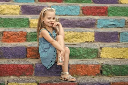Niña pequeña o niño lindo con adorable cara sonriente y lazo en cabello rubio con vestido azul sentado al aire libre en el fondo de coloridas escaleras pedregosas, espacio de copia