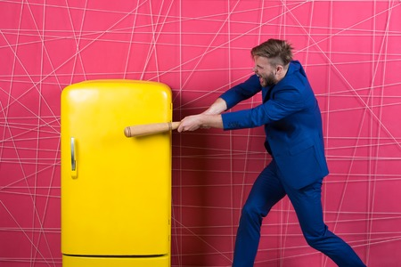By force or persuasion. man in stylish jacket. confident businessman in suit. Businessman with bat hit yellow fridge. angry man. Feel the success. Business fashion. Male formal fashion.