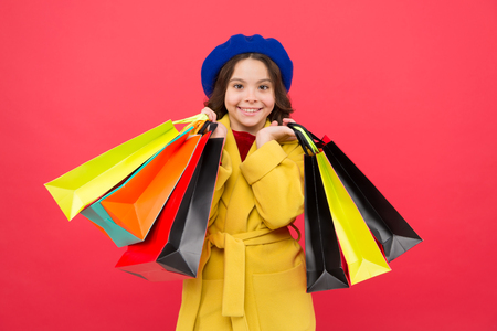 Get discount shopping on birthday holiday. Fashionista adore shopping. Obsessed with shopping. Get major wardrobe refresh with spring sales at stores. Girl cute kid hold shopping bags red background.