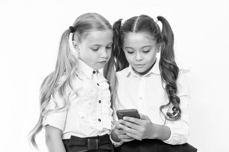 Kleine Kinder sind auf das Handy angewiesen. Mädchen-SMS mit Handy. abhängen