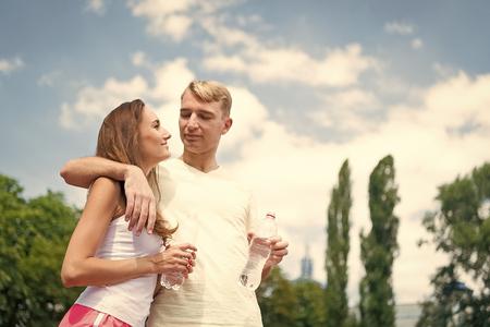 Mujer y hombre beben agua de botella. Chica y chico soleado al aire libre. Actividad de verano y energía. Par de entrenador relajarse después del ejercicio. Deporte y salud. Foto de archivo