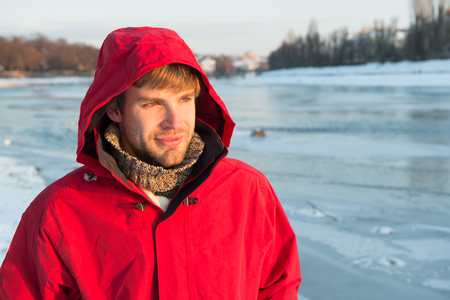 Happy winter holidays. Flu and cold. Sexy man in winter clothes. Winter fashion. red warm coat. Warm clothes for cold season. Man traveling in winter, nature. Look at this. copy space.