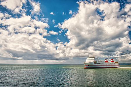 Ship in sea on cloudy blue sky. Seascape with ocean liner and clouds. Summer vacation, adventure and wanderlust concept. Water transport for transportation, travelling.