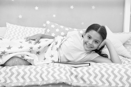 Satisfied with happy end. Girl child lay bed read book. Kid prepare to go to bed. Pleasant time in cozy bedroom. Girl kid long hair cute pajamas relax and read book. She likes kind stories about love.