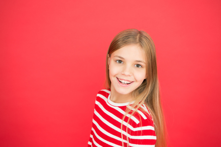 Good parenting. Child care. family and love. childrens day. happy little girl on red background. small girl child. School education. Childhood happiness. copy space. Little daydreamer.