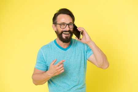 Stay in touch. Man bearded cheerful mature guy hold mobile phone yellow background. Hipster smartphone call partner. Man mobile call smartphone. Mobile call concept. Important mobile conversation.