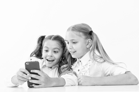Modern life concept. Little children girls study smartphone as integral part of modern life. little girls with cell phone