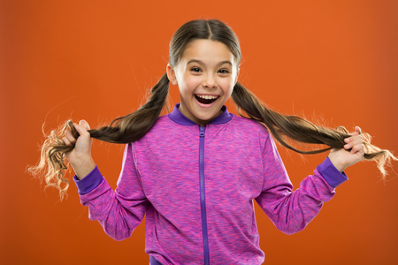 childhood happiness. Family. Kid fashion and sportswear. Happy little girl with long hair. childrens day. Portrait of happy little child. Small girl child. Hairdresser for kids. Little daydreamer. Stock Photo