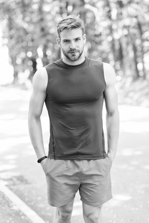 Enjoy wellbeing and healthy body. Man sporty outfit looks confident outdoors nature background. Guy bearded muscular body proud of his shape. Sportsman enjoy his muscular body proud of himself.