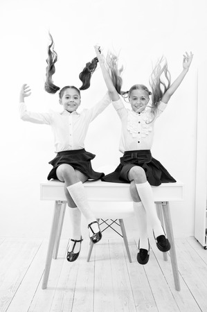 School break concept. Schoolgirls cute pony tails hairstyle sit on desk. Best friends free having fun play with hair. Perfect schoolgirls with tidy fancy hair. School hairstyles ponytails in mid air.