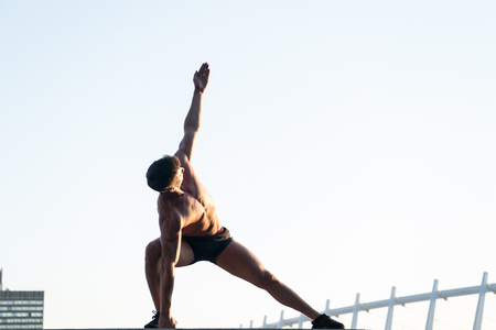 Man stretching hands and legs on roof. Sportsman with muscular body on white sky. Athlete doing workout outdoors. Fitness and sport. Healthy lifestyle concept, copy space Stock Photo