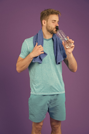 Man drink water after training on violet background. Thirsty sportsman with plastic bottle on purple background. Thirst and dehydration. Drinking water for health. Sport activity and energy. Imagens
