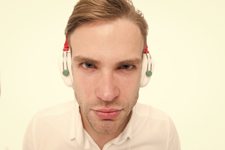 I can not hear you. Guy with earphones listens music. Man concentrated face listening favourite song in headphones. Man serious strict face busy listening music isolated white background.