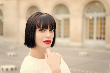 Woman with brunette hair and red lips makeup face in Paris, France.