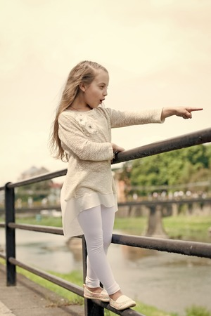 Kid girl with long hair walks near riverside, river on background. Girl child tourist enjoy sightseeing while walks. Vacation concept. Girl or schoolgirl on vacation enjoy travelling and sightseeing.