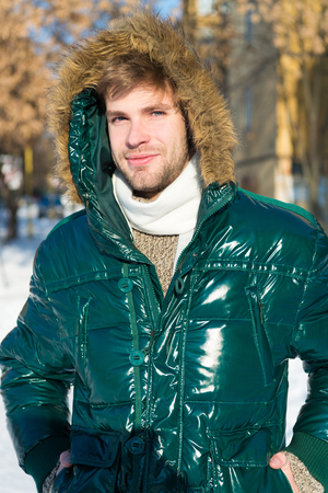 Prepared for weather changes. Winter stylish menswear. Winter outfit. Man unshaven wear warm jacket with fur snowy nature background. Guy wear winter jacket with furry hood. Hipster winter fashion.