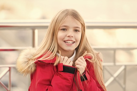 Child in red coat stand on bridge. Kid enjoy autumn day on blurred environment. Girl with blond long hair smile outdoor. Adventure, discovery, journey. Vacation, travelling concept.