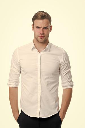 Jung und selbstbewusst. Mann gut gepflegt aufgeknöpft weißen Kragen elegantes Hemd isoliert weißen Hintergrund. Macho zuversichtlich bereit Arbeitsbüro. Guy Büroangestellter gut aussehend attraktiv legt Hände Taschen.