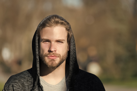 Lifestyle for active and healthy man, sport. Macho with beard in hood on sunny day. Bearded man wear casual sweatshirt outdoor. Fashion guy in stylish sportswear.