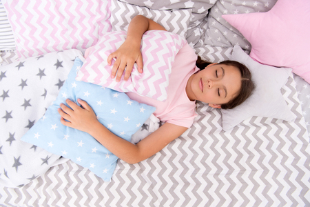 Fall asleep as fast as possible. Fall asleep faster and sleep better. Healthy sleep. Sweet dreams. Girl child lay bed pillow and blanket bedroom top view. Lullaby concept. Ways to fall asleep faster. Standard-Bild
