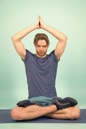 Sportsman relax in lotus pose. Man meditate on yoga mat. Fashion athlete practice yoga in gym. Meditation for body and mind health. Meditation or zen and peace concept.