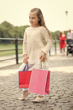 Little girl with shopping bags on street. Child with paper bags outdoor. Kid shopper in fashion clothes. Holidays preparation and celebration. All I got on sale. Shopping and black friday.