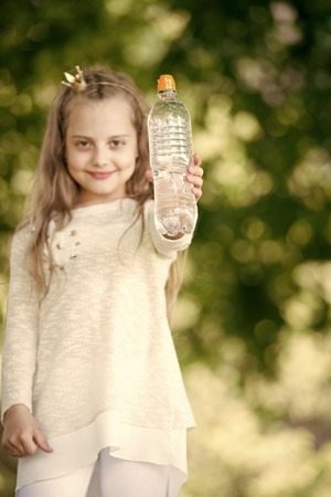 Lovely happy little princess girl with water showing yes gesture on natural background Stock Photo