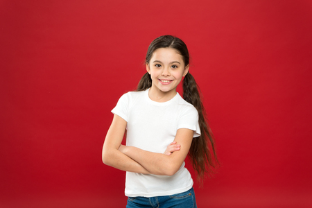 She is really cute. Fashion look of small model. Little fashionista. Fashion girl on red background. Adorable girl child in casual style. Little kid with stylish long hair. Happy small child. Imagens