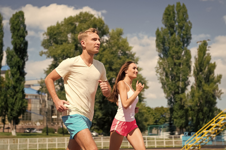 Couple running on arena track. Man and woman sunny outdoor on blue sky. Coach and trainer at workout. Runner on competition and future success. Sport and healthy fitness.