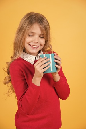 Tea or coffee break. Child smile with blue cup on orange background. Thirst, dehydration concept. Health and healthy drink. Girl with long blond hair in red sweater hold mug.