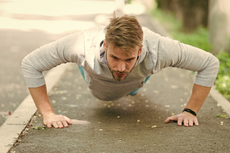 Strength and motivation. Man in sportswear doing push ups outdoor. Guy motivated workout in park. Sportsman improves his strength by push up exercise. Man has motivation to success sport achievement. Stock Photo