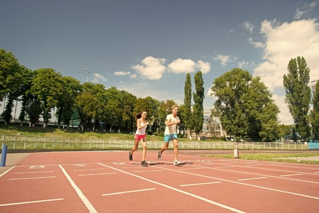 Sport and healthy fitness. Coach and trainer at workout. Runner on competition and future success. Man and woman sunny outdoor on blue sky. Couple running on arena track.
