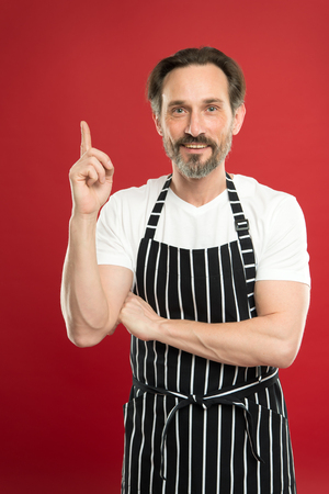 Man in apron. Confident mature handsome man in apron red background. He might be baker gardener chef or cleaner. Good in everything. Multitasking and professional occupation. Apron for dirty work. Stok Fotoğraf